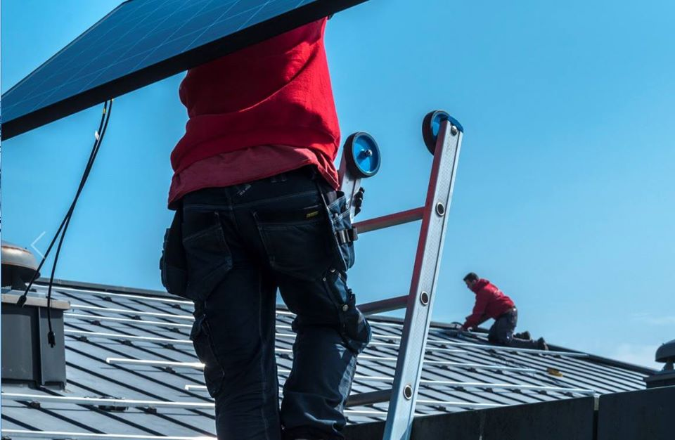 Rensol installateur op een dak die een zonnepaneel draagt