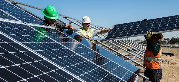 Drie installateurs installeren zonnepanelen